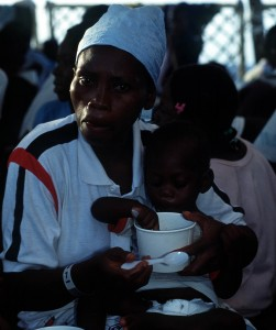 Two Haitian refugees eat rice on board a U.S. Coast Guard cutter.  USCG photo by RESSLER, ROBIN PA2