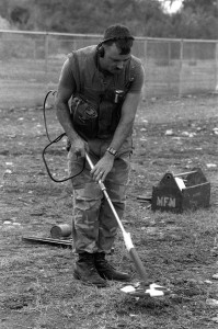 Maintenance Section, uses a metallic mine detector to locate mines under the ground during training at Guantánamo. Courtesy Records of the Office of the Secretary of Defense.