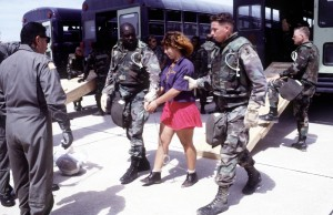 Shackled refugee escored by military